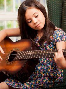 little girl learning guitar